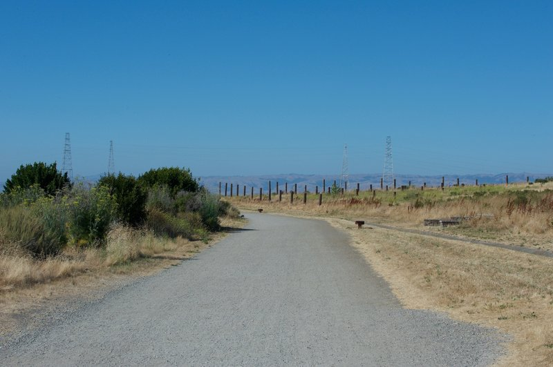 The trail departs the parking lot via a wide, gravel trail that leads out to the South San Francisco Bay.