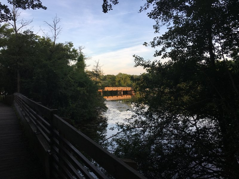 View of walking bridge toward wooden vehicle bridge.