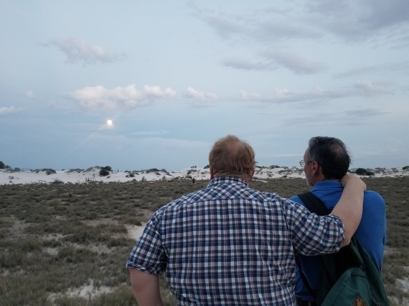 "Watching the moon rise on the White Sands National Monument's ""Full Moon Hike,"" held each month during the full moon."