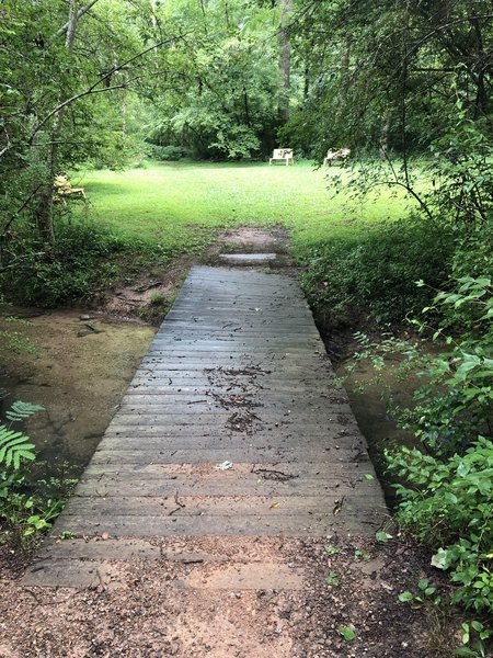 The wooden bridge into the clearing with benches.