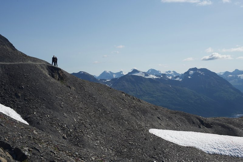 The trail narrows and wraps around the hillside and offers sweeping views of the mountains of the Kenai Peninsula.