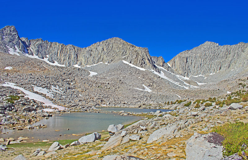 At 11,200 feet, this is the highest of the lakes in Pioneer Basin. It is a large lake that extends behind the very low ridge on the right side.