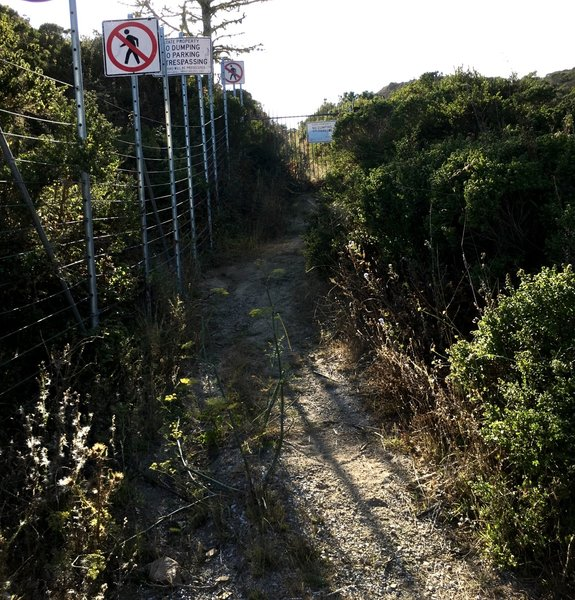 Access to trail around black gate is blocked by wire fence