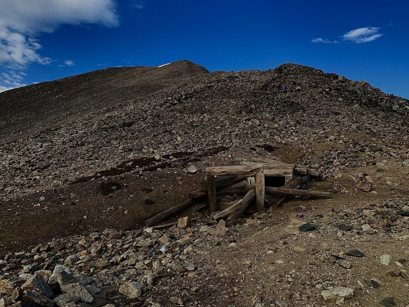Turn left at the saddle between Mount Democrat & Cameron. Silver was first discovered here in ca. 1874. Abandoned mines are a regular feature. Stay on the marked Trail!