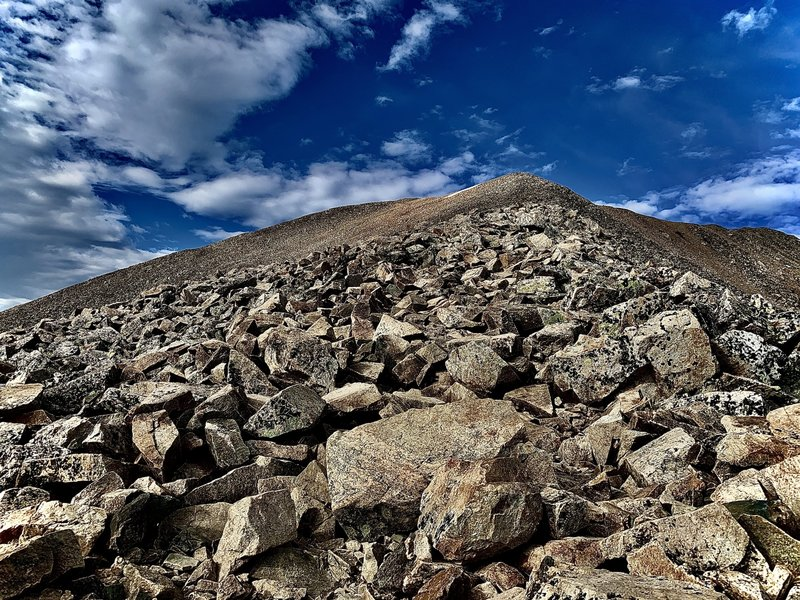 Above the saddle of Mount Cameron, this is your view up towards the false summit of Mount Democrat. Keep going and that snowfield dip down is your way up to the Summit. (Farther than it looks,  closer than it appears). Pay Attention! now to the weather!