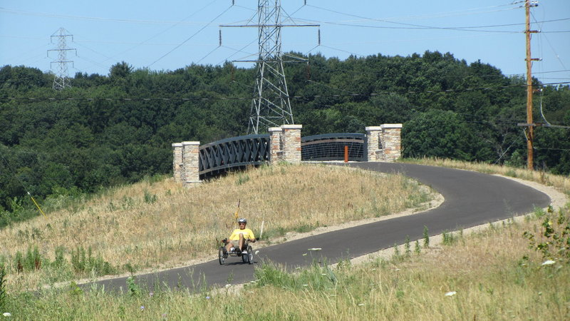 """Recumbent Trike At Bridge Over Maynard"""" by John Eisenschenk (https://tinyurl.com/u4emtb8), Flickr licensed under CC BY 2.0 (https://creativecommons.org/licenses/by/2.0/)."""
