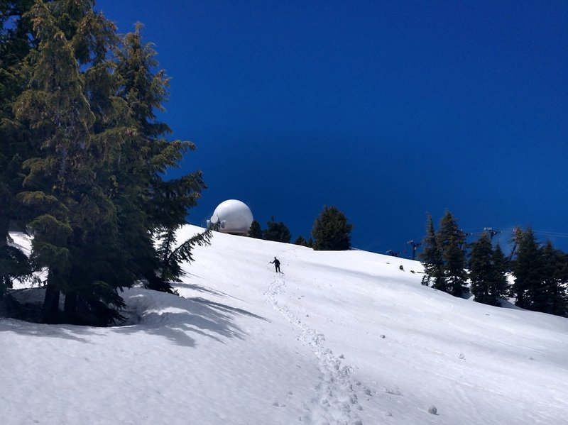 Descending the trail in early season when the ski area is closed but there's still snow cover up high