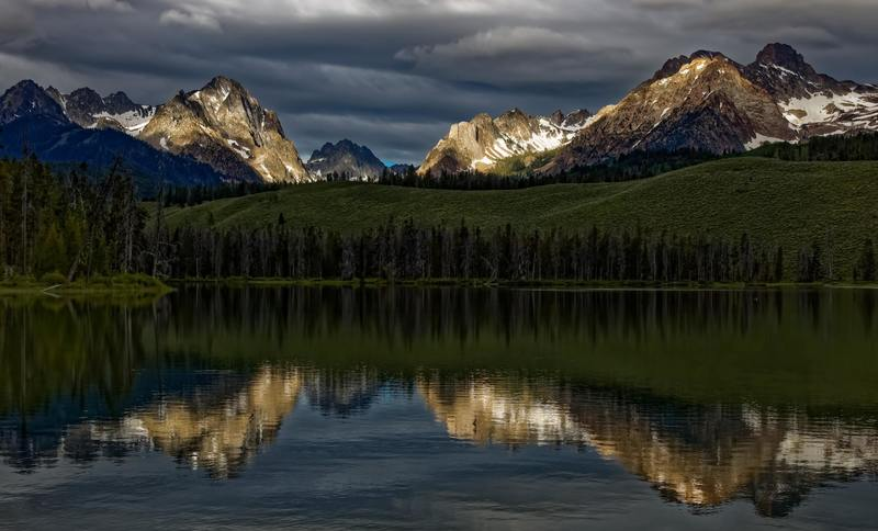 While out early exploring the Sawtooth Mountains near Stanley, Idaho I came across this scene where the first rays of morning light accentuating the mountain peaks.