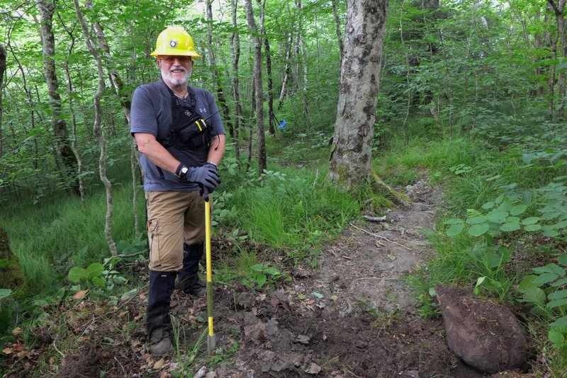 Volunteer trail maintainer builds steps on the trail leading to Bob Bald