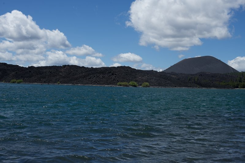 Cinder Cone rises in the distance as the Fantastic Lava Beds come right up to the water.  Kayakers, paddleboarders, and fishermen can be seen on the lake.