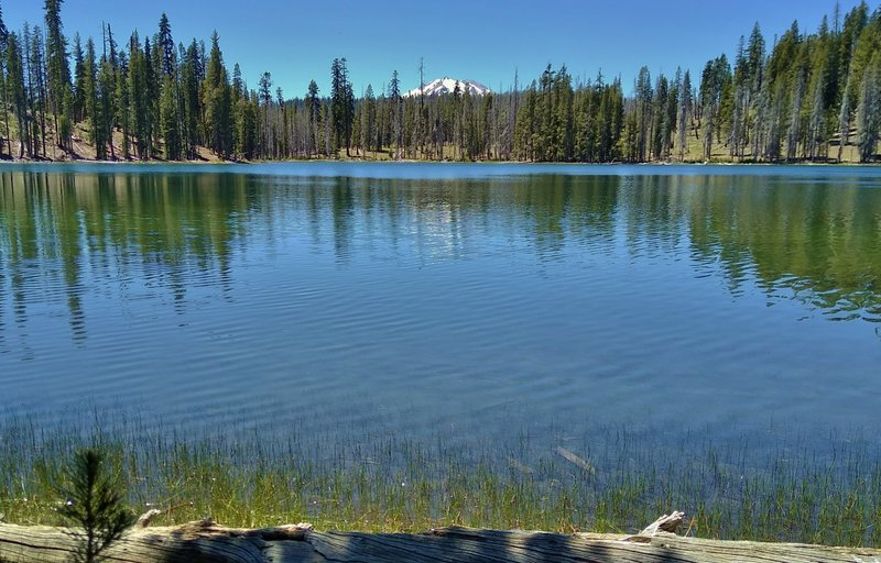 Lassen Peak in the distance to the west, is seen across Rainbow Lake close to Rainbow Lake Trail.