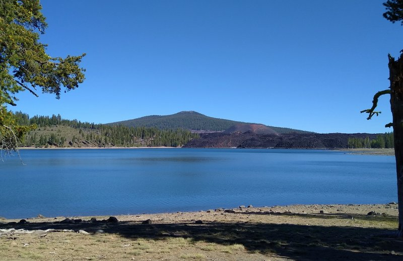 Prospect Peak, 8,338 ft., is the forested mountain in the distance. In front of Prospect Peak's right shoulder is Cinder Cone, and in front of Cinder Cone are the black boulders of Fantastic Lava Beds. Seen looking northwest across Snag Lake.