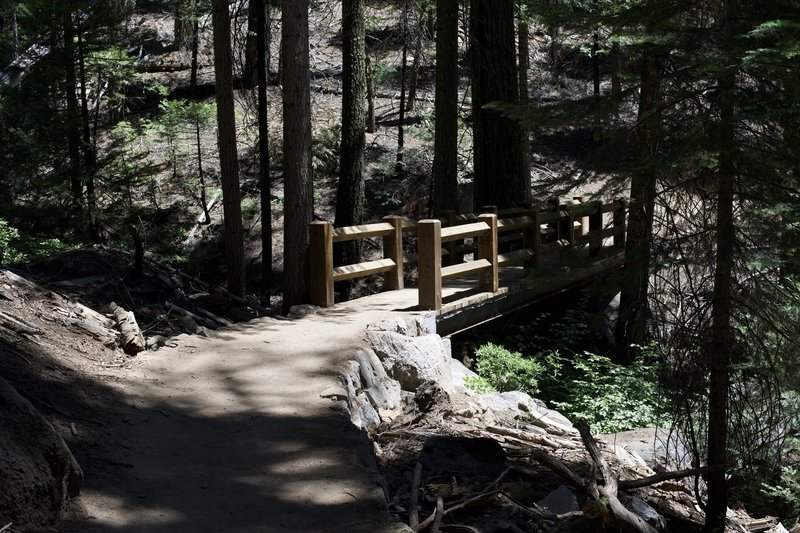 A bridge crosses a small creek as it makes its way up to the Mariposa Grove parking area.