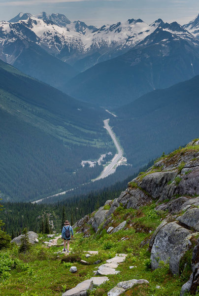 A hiker descends the Hermit Trail towards the Roger's Pass.