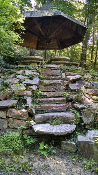 Stone steps leading to a grindstone table picnic area on the Chinqua-Penn Walking Trail.