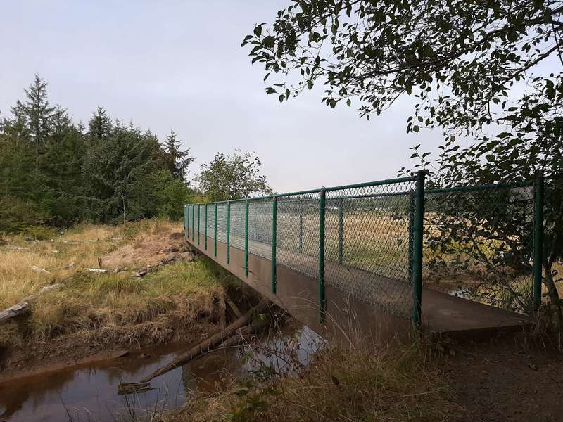 A bridge over a creek with fenced railings.