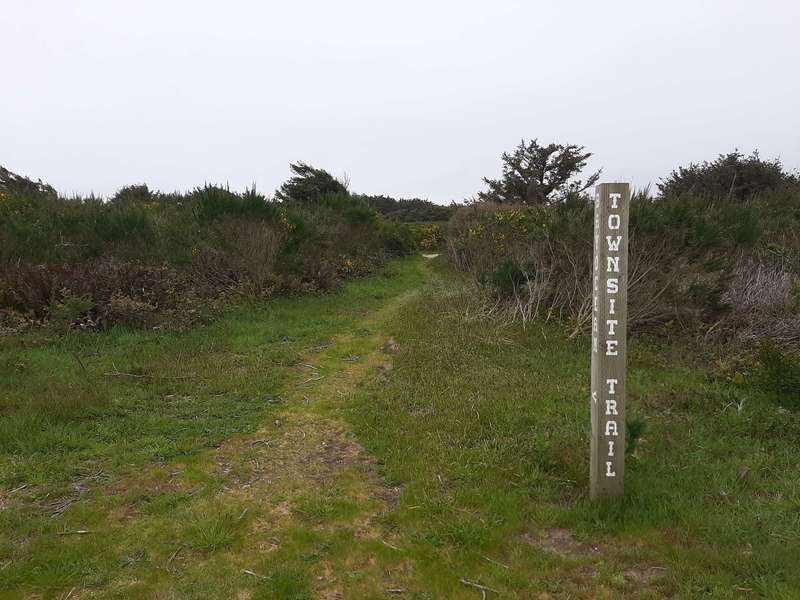 Tall wooden sign marking the trail.