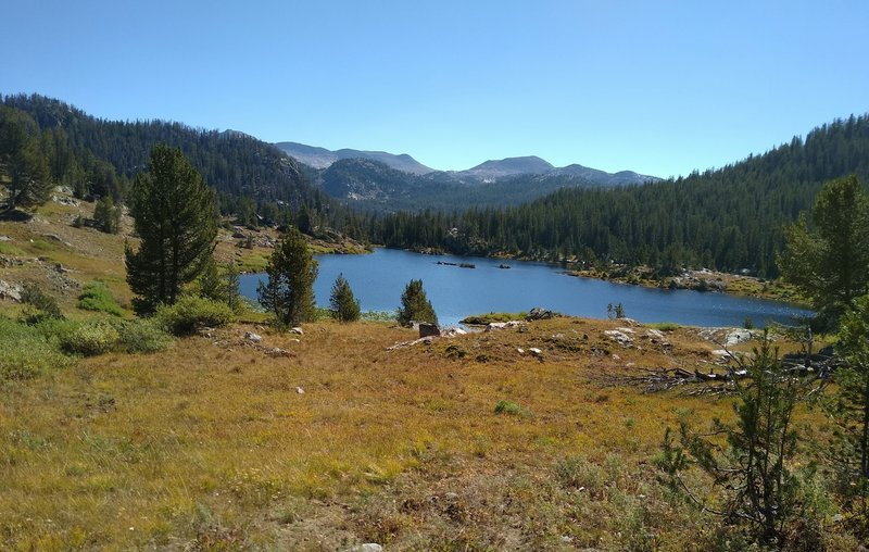 One of many small lakes in the high country, passed by Summit Lake Trail. Rugged peaks of the Wind Rivers are seen in the distance to the east here.