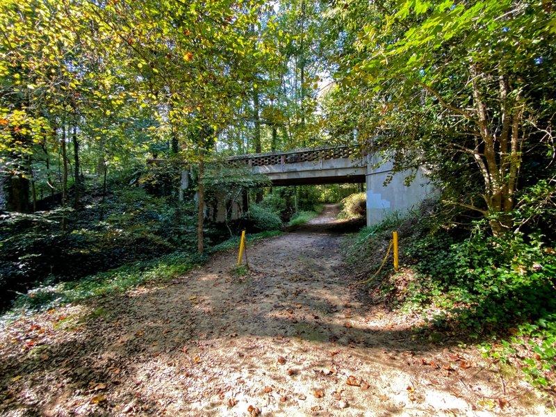 A bridge rising above the trail.