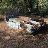 An old car sits along the side of the trail, flipped over and spray painted.
