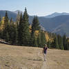 Hiker crossing an alpine meadow framed by the Taos Ski Area mountains