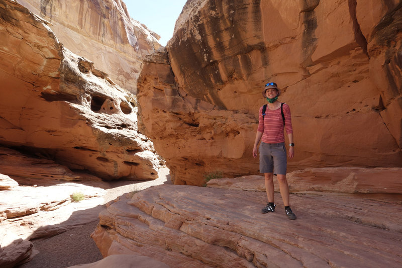 Hiker posing on a shaded slickrock ledge in Bell's Canyon.
