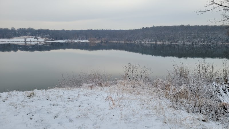 The trail opens out onto a small clearly right at the edge of Lake Jacomo providing an expansive view of the water.