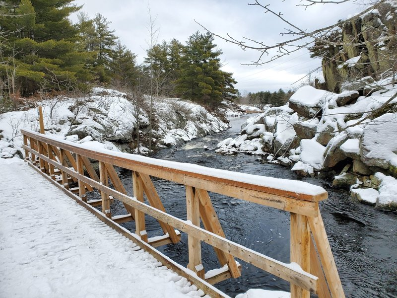 Peaceful snowy bridge and river.