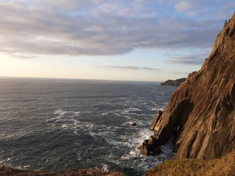 A sea cliff with waves crashing against it close to sunset.