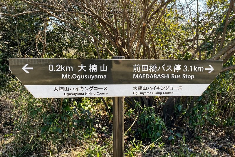 A sign near the top of Mt. Ogusu showing the direction and distance to the Maedabash bus stop via the trail to the Maedagawa Promenade.