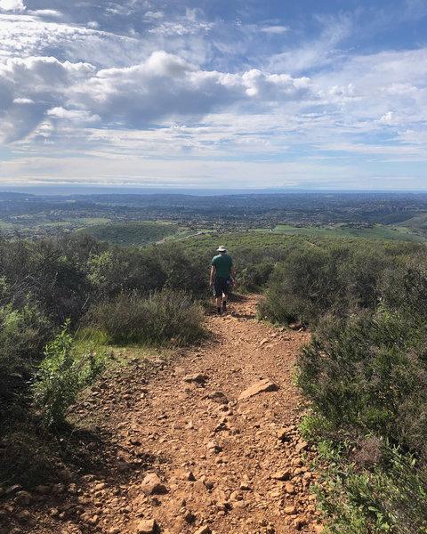 Hiker on Black Mountain, facing toward the Santaluz Club with Rancho Santa Fe in the far background.