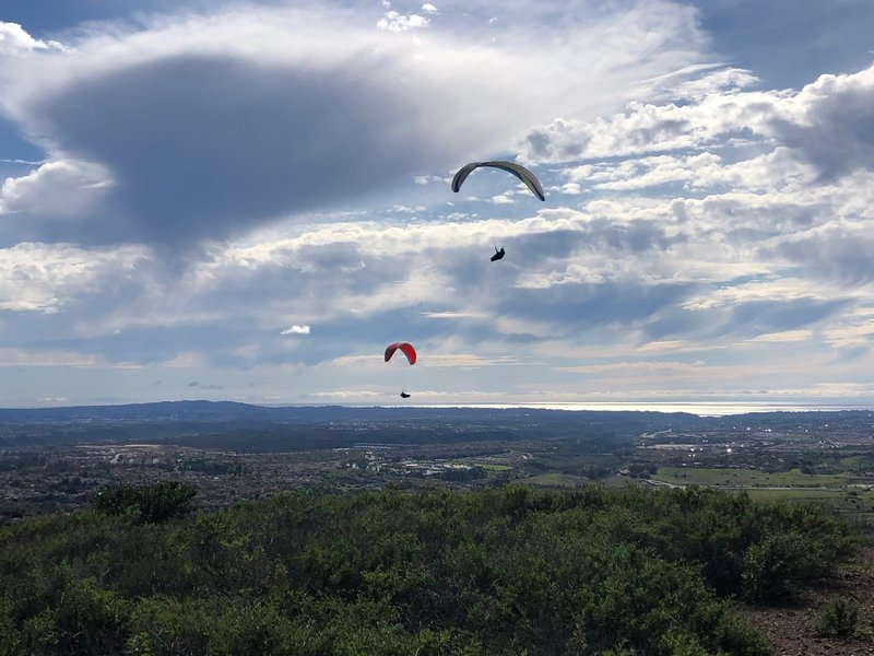 Two paragliders on the western edge of Black Mountain with Torrey Highland in the distance and the Pacific Ocean 10 miles away. Downtown La Jolla is just left of the lower paraglider.