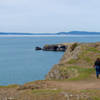 Hikers walking along the cliffs of Rosario Head