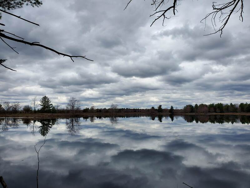 Cloudy skies reflected on a still lake.
