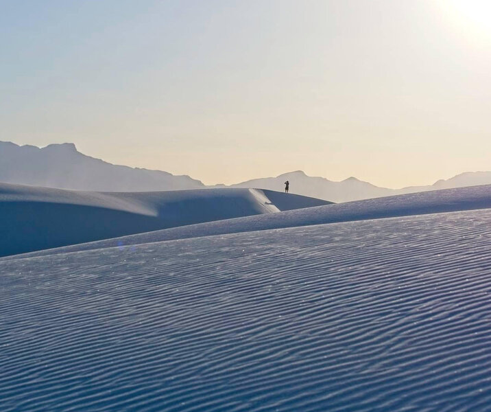 Lone hiker on the windswept dunes of White Sands NP