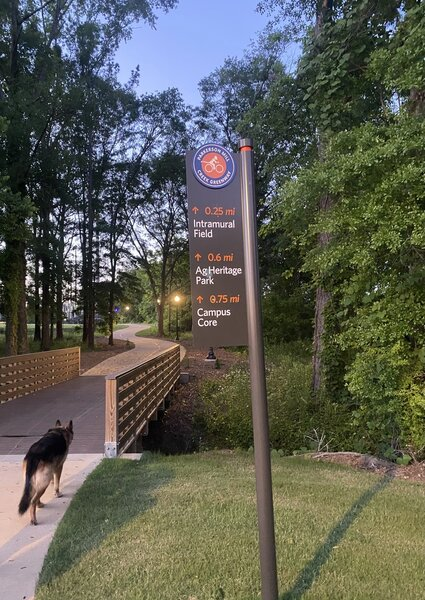 Directional sign for the Parkerson Mill Creek Greenway right before a small foot bridge.
