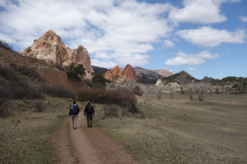 Two hikers on the Ute trail walking in the direction of Gray Rock (left) and the Gateway Rocks (center) at Garden of the Gods.