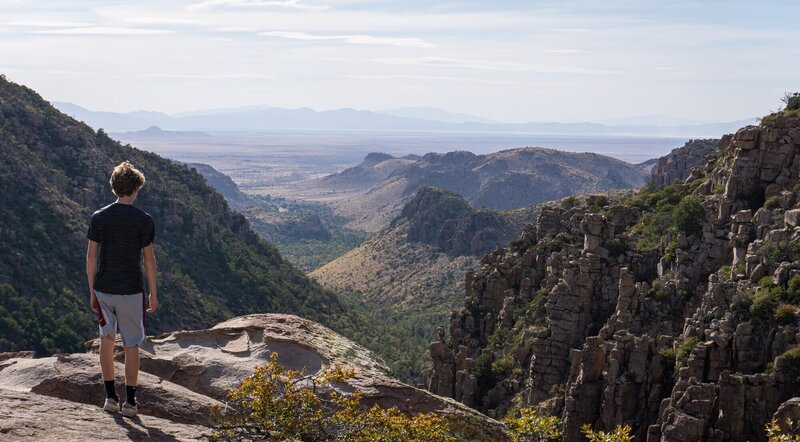 A hiker looking out from the edge of the Chiricahua Mountains.
