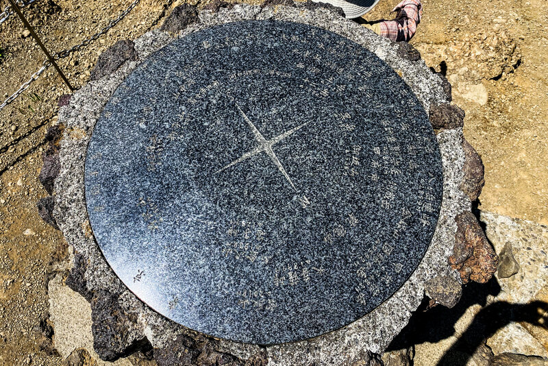 The compass pointing out the other mountains at the summit.