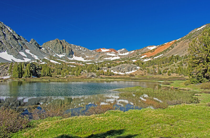 The first of the 3 Frog Lakes. Some of the mineral rich soils appear brilliant orange in direct morning or evening sunlight. Burro Pass in the low point in the ridge in front of the orange mountain.