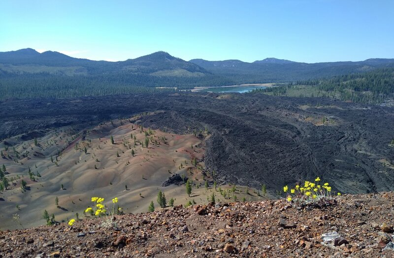 From the rim of Cinder Cone looking south-southeast: Snag Lake in the distance, Mt. Harkness behind right/south end of Snag Lake, Mt. Hoffman (upper center left), Red Cinder and Red Cinder Cone (upper left), Painted Dunes and Fantastic Lava Beds below.