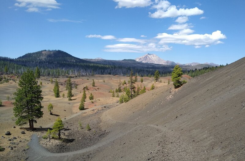 The trail goes down and winds through the Painted Dunes. On the horizon are nearby Fairfield Peak (left) and Lassen Peak center right.