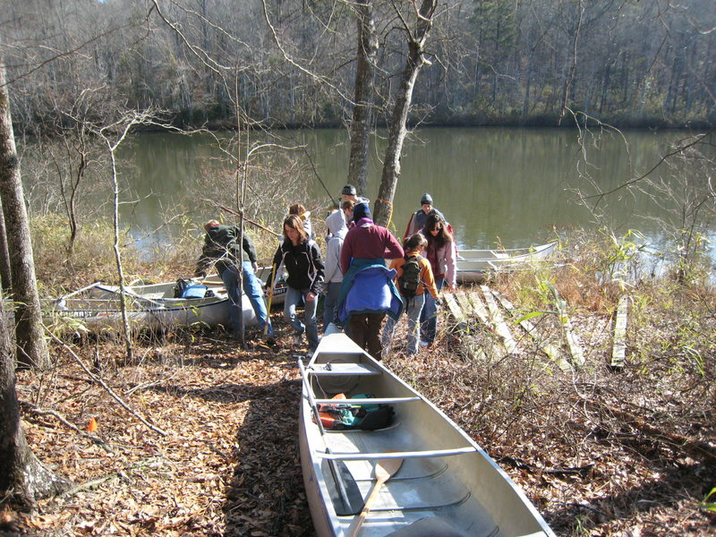 "University of Alabama Honors College trail work crew transporting material to replace the ""bridge to far"". Due to the remoteness of the west side of the park often the easiest or only way to get to a work site is to cross the lake by boat or canoe then hike."