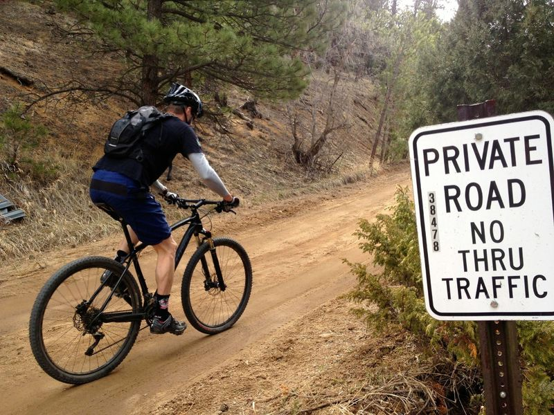 This terribly misleading sign means you're in the right place.  This road is absolutely open to public hiking and biking.  Rural Boulder County roads are full of these misleading signs that should be taken down.  The land around the road is public, you have every right to be on the road!