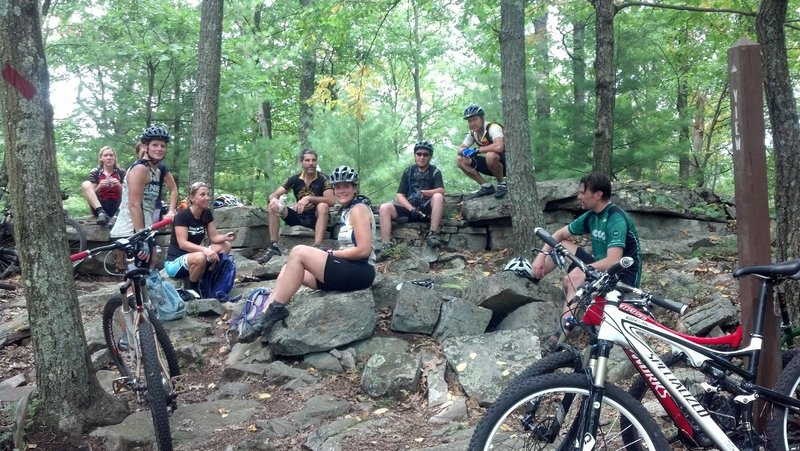 NMBA members taking a break on the natural rock benches after a hot humid climb on Deer Tick before continuing on to Beautiful trail