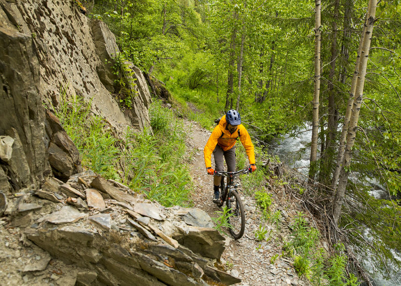 Narrow singletrack flanked one one side by stone walls and the other by Crescent Creek