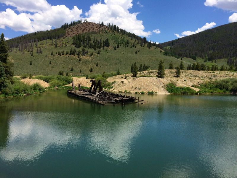 One of the historic dredge boats from the early 1900's the piled up mountains of river rock in the search for gold flakes.