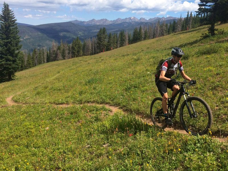 Cruising up Mid Vail Escape with the Gore Range in the distance.