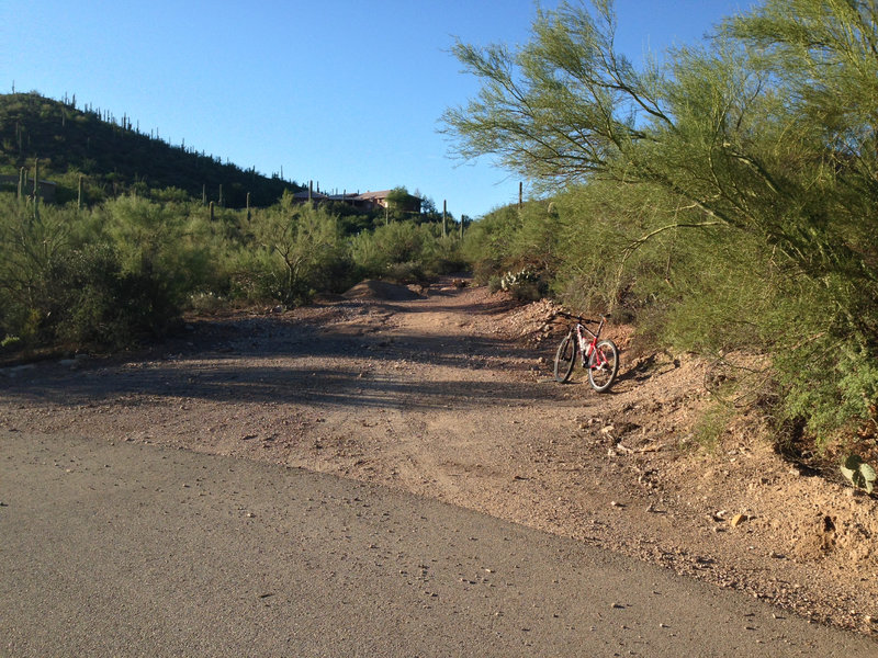 The unmarked exit from paved road onto singletrack on the Robles Loop from Genser Trailhead. Photo is looking south.
