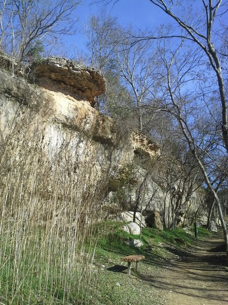 Scenic overhanging rocks and park benches along the pack gravel section of North San Gabriel River Trail